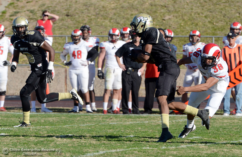 . Butte College\'s #1 Wes McCoy (center) breaks the tackle against Fresno City College\'s #38 Cedric Castro (right) to return a kickoff for a touchdown in the third quarter of their football game at Butte\'s Cowan Stadium Saturday, November 30, 2013 in Butte Valley, Calif.  (Jason Halley/Chico Enterprise-Record)
