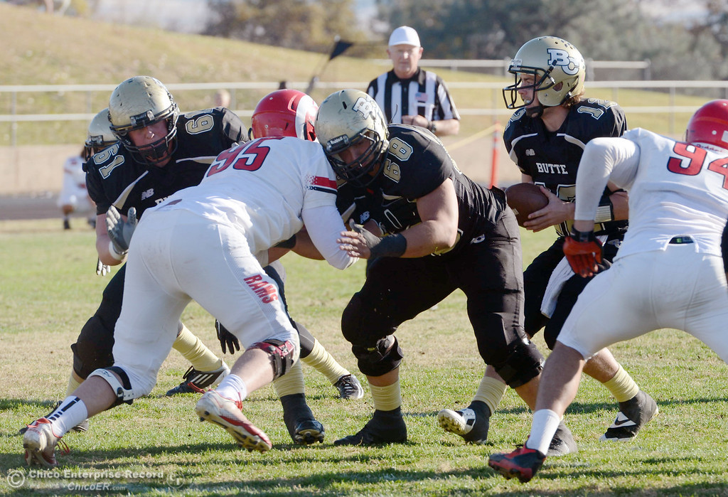 . Butte College\'s #12 Thomas Stuart (far right) takes the snap as #61 Jacob Bigham (left) and #68 Eli Thom (center) block against Fresno City College\'s #95 Wyatt McBee (center) in the third quarter of their football game at Butte\'s Cowan Stadium Saturday, November 30, 2013 in Butte Valley, Calif.  (Jason Halley/Chico Enterprise-Record)