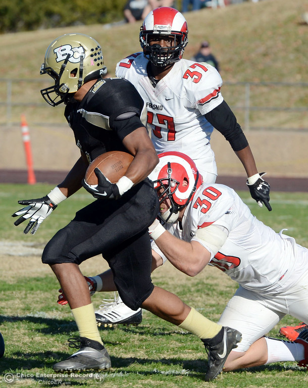 . Butte College\'s #21 Marvel Harris (left) is tackled against Fresno City College\'s #30 Tyler Bates (right) as #37 Gerald Nutt (back) looks on in the third quarter of their football game at Butte\'s Cowan Stadium Saturday, November 30, 2013 in Butte Valley, Calif.  (Jason Halley/Chico Enterprise-Record)