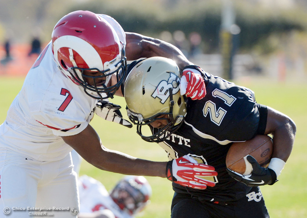. Butte College\'s #21 Marvel Harris (right) is tackled against Fresno City College\'s #7 Vadal McDonald (left) in the first quarter of their football game at Butte\'s Cowan Stadium Saturday, November 30, 2013 in Butte Valley, Calif.  (Jason Halley/Chico Enterprise-Record)