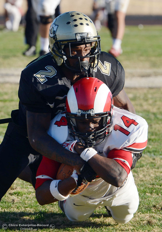 . Butte College\'s #2 Deonte Flemings (top) tackles Fresno City College\'s #14 Darius Armstead (bottom) in the fourth quarter of their football game at Butte\'s Cowan Stadium Saturday, November 30, 2013 in Butte Valley, Calif.  (Jason Halley/Chico Enterprise-Record)