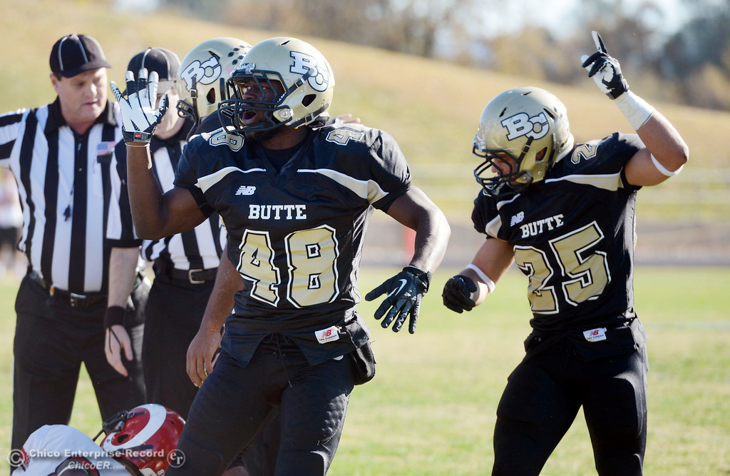 . Butte College\'s #48 Michael Faggett (left) and #25 De\'Aundray Gooden (right) gesture recovered fumble against Fresno City College in the first quarter of their football game at Butte\'s Cowan Stadium Saturday, November 30, 2013 in Butte Valley, Calif.  (Jason Halley/Chico Enterprise-Record)