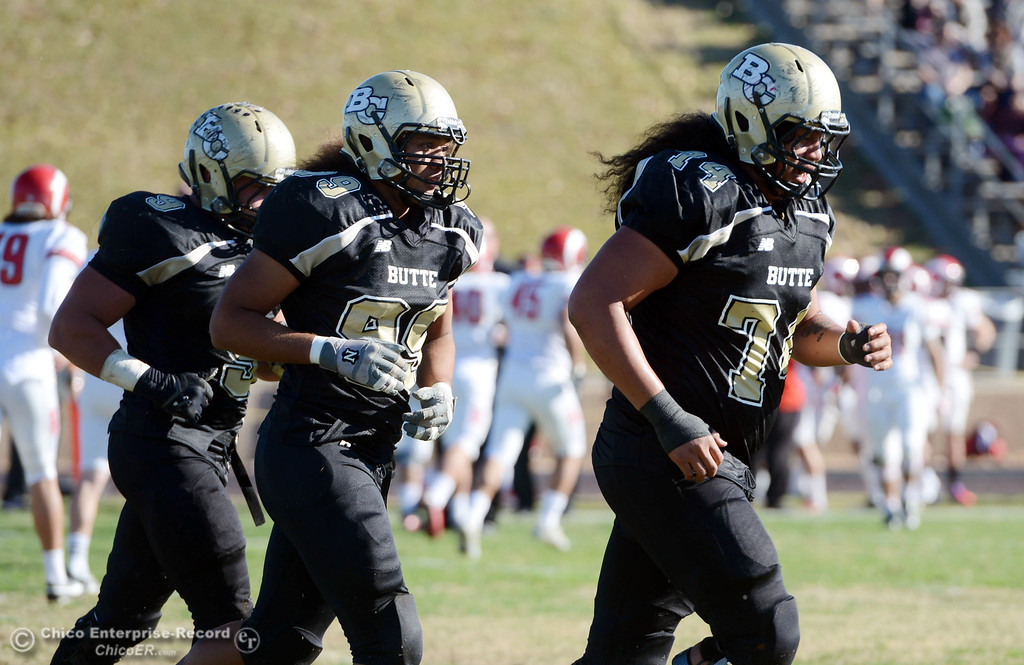 . Butte College\'s #9 Tyler Adair, #99 Leopeni Siania and #74 Christopher SIliga (left to right) come off the field against Fresno City College in the second quarter of their football game at Butte\'s Cowan Stadium Saturday, November 30, 2013 in Butte Valley, Calif.  (Jason Halley/Chico Enterprise-Record)