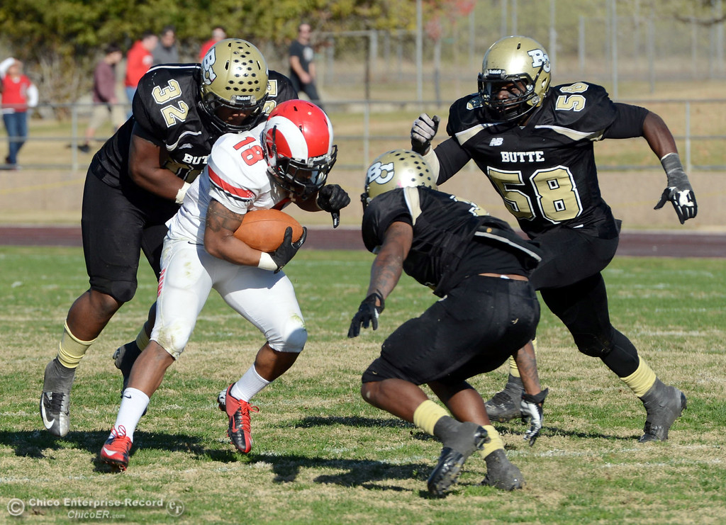 . Butte College\'s #32 Brian Anderson, #2 Deonte Flemings, and #58 Sie Doe Jr (left to right) tackle against Fresno City College\'s #18 Micah Ledezma in the third quarter of their football game at Butte\'s Cowan Stadium Saturday, November 30, 2013 in Butte Valley, Calif.  (Jason Halley/Chico Enterprise-Record)