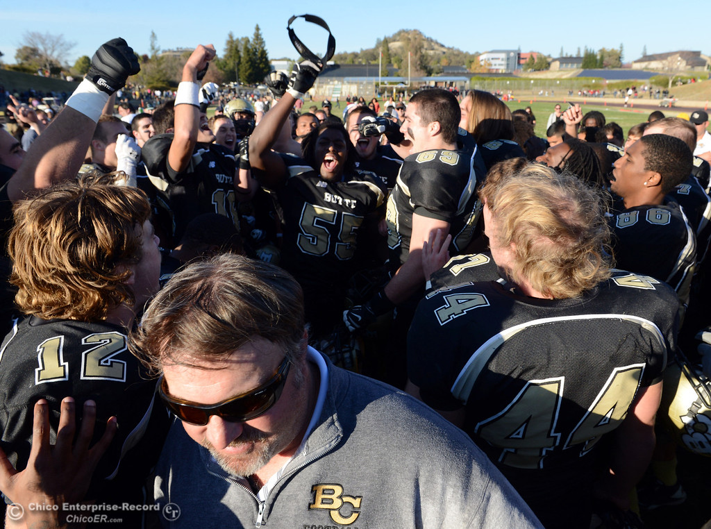 . Butte College head coach Jeff Jordan (bottom) walks out as the team celebrate in their win against Fresno City College at the end of their football game at Butte\'s Cowan Stadium Saturday, November 30, 2013 in Butte Valley, Calif.  (Jason Halley/Chico Enterprise-Record)