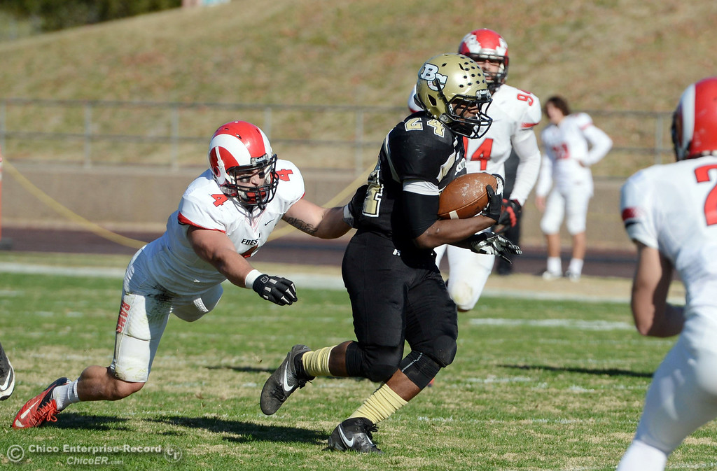 . Butte College\'s #24 Kendall Williams (right) rushes against Fresno City College\'s #4 Isaac Sarate (left) in the second quarter of their football game at Butte\'s Cowan Stadium Saturday, November 30, 2013 in Butte Valley, Calif.  (Jason Halley/Chico Enterprise-Record)