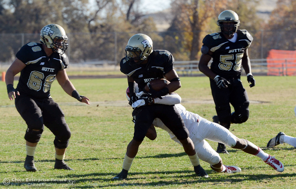 . Butte College\'s #1 Wes McCoy (left) is tackled against Fresno City College\'s #8 Justice Sarcedo (right) in the third quarter of their football game at Butte\'s Cowan Stadium Saturday, November 30, 2013 in Butte Valley, Calif.  (Jason Halley/Chico Enterprise-Record)