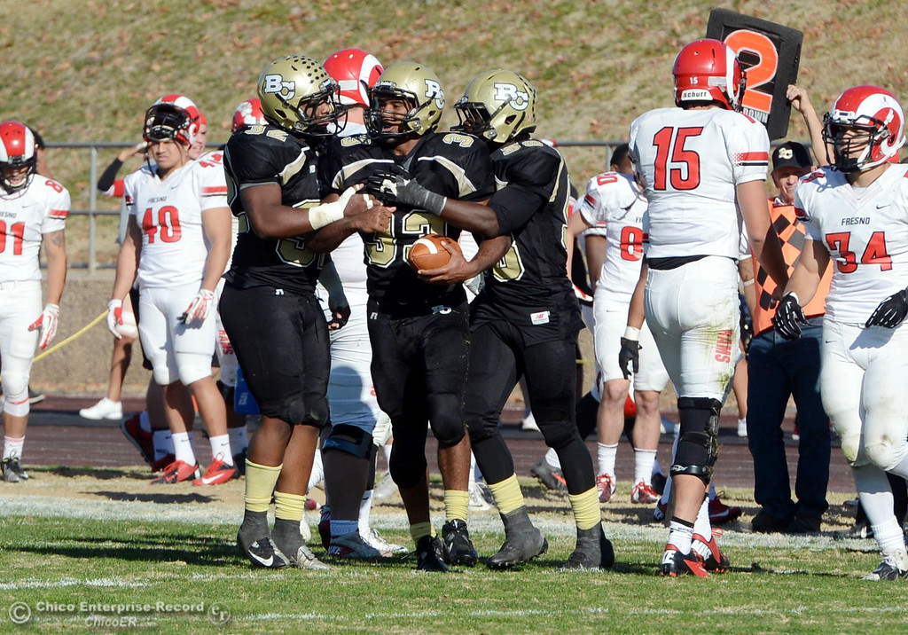 . Butte College\'s #32 Brian Anderson (left) celebrates #33 Jariah Booker (center) who picks up an interception with #58 Sie Doe Jr. (right) against Fresno City College in the second quarter of their football game at Butte\'s Cowan Stadium Saturday, November 30, 2013 in Butte Valley, Calif.  (Jason Halley/Chico Enterprise-Record)