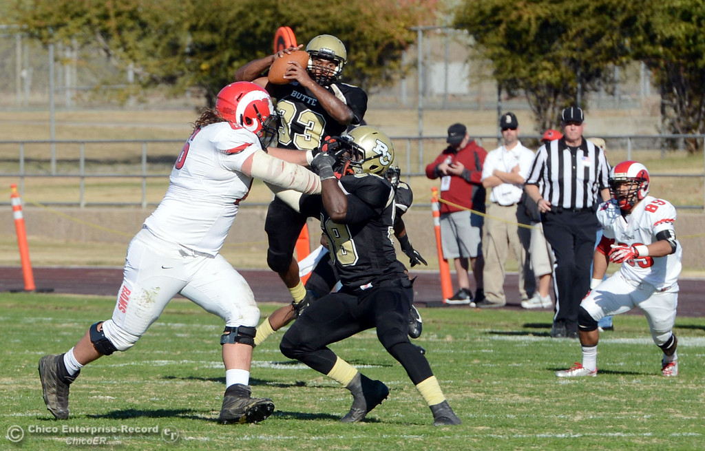 . Butte College\'s #33 Jariah Booker picks up an interception against Fresno City College in the second quarter of their football game at Butte\'s Cowan Stadium Saturday, November 30, 2013 in Butte Valley, Calif.  (Jason Halley/Chico Enterprise-Record)