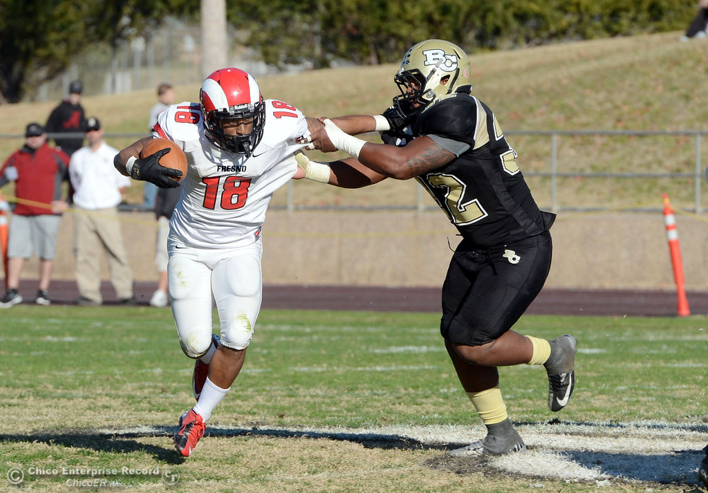 . Butte College\'s #32 Brian Anderson (right) tackles against Fresno City College\'s #18 Micah Ledezma (left) in the third quarter of their football game at Butte\'s Cowan Stadium Saturday, November 30, 2013 in Butte Valley, Calif.  (Jason Halley/Chico Enterprise-Record)