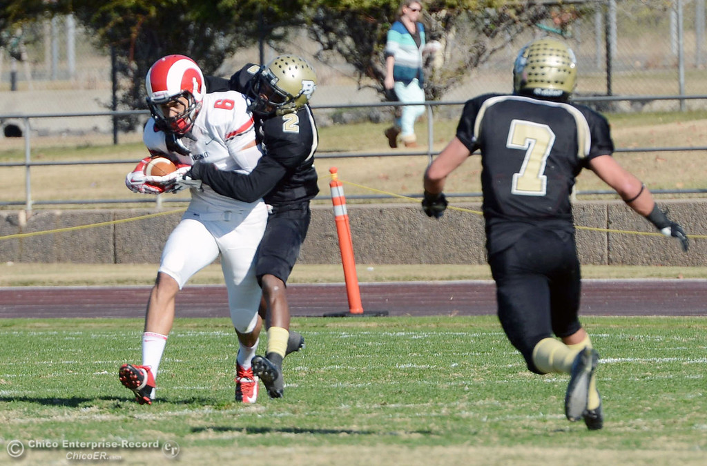 . Butte College\'s #2 Deonte Flemings (center) tackles against Fresno City College\'s #8 Justice Sarcedo (left) in the first quarter of their football game at Butte\'s Cowan Stadium Saturday, November 30, 2013 in Butte Valley, Calif.  (Jason Halley/Chico Enterprise-Record)