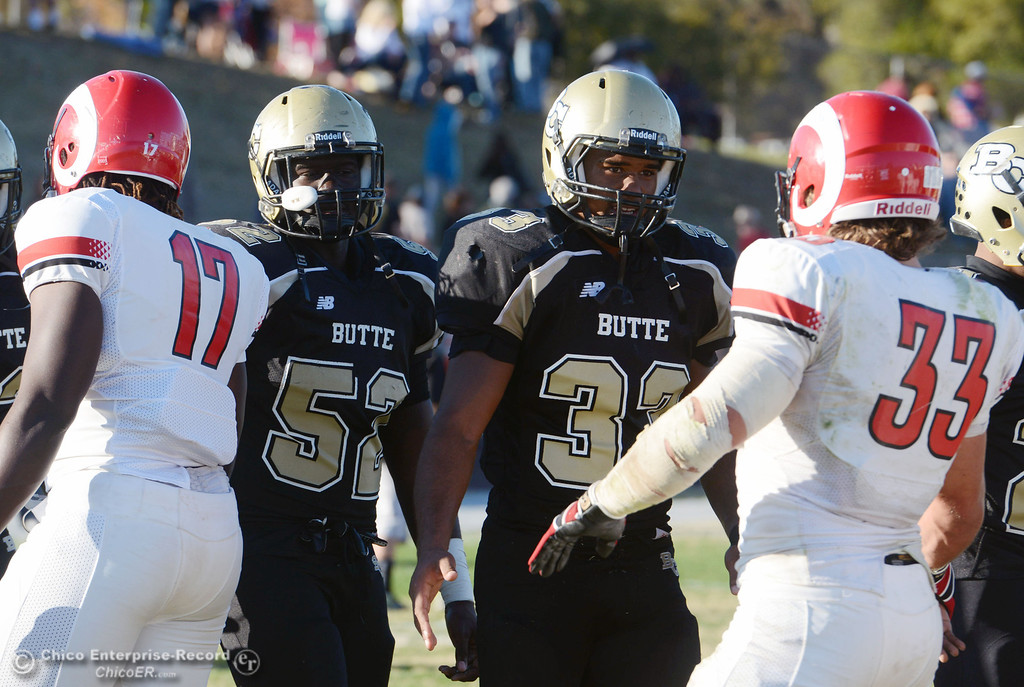 . Butte College\'s #52 Kyjuan Tate (left) and #33 Jariah Booker (right) shake hand with Fresno City College\'s #17 Ferlindo Vincent (left) and #33 Dakota Gordon (right) at the end of their football game at Butte\'s Cowan Stadium Saturday, November 30, 2013 in Butte Valley, Calif.  (Jason Halley/Chico Enterprise-Record)