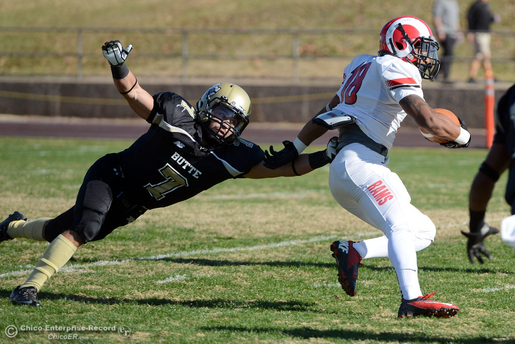 . Butte College\'s #7 Ryan Holland (left) tackles against Fresno City College\'s #18 Micah Ledezma (right) in the first quarter of their football game at Butte\'s Cowan Stadium Saturday, November 30, 2013 in Butte Valley, Calif.  (Jason Halley/Chico Enterprise-Record)