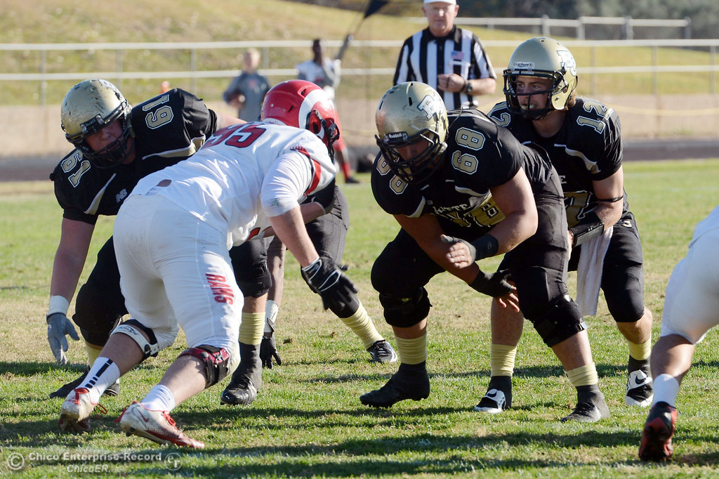 . Butte College\'s #68 Eli Thom (left) snaps to #12 Thomas Stuart (right) against Fresno City College in the third quarter of their football game at Butte\'s Cowan Stadium Saturday, November 30, 2013 in Butte Valley, Calif.  (Jason Halley/Chico Enterprise-Record)