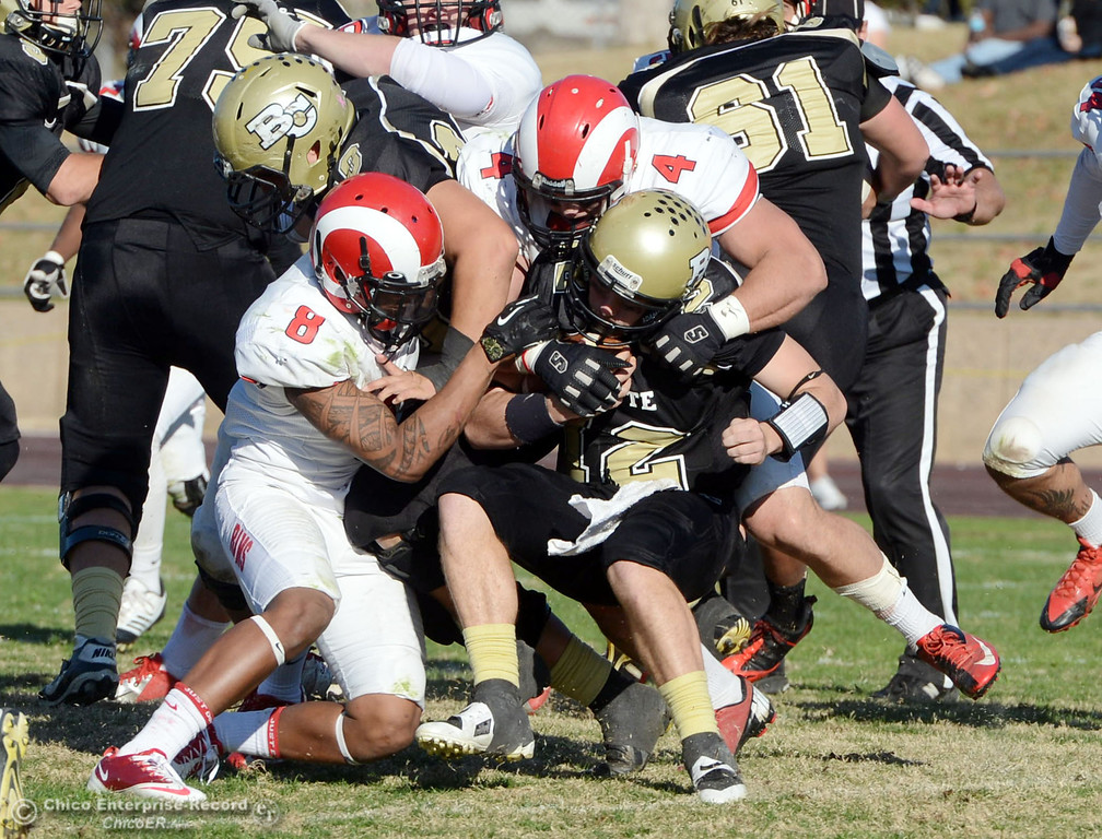 . Butte College\'s #12 Thomas Stuart (center) is tackled against Fresno City College\'s #8 Justice Sarcedo (left) and #4 Isaac Sarate (right) in the third quarter of their football game at Butte\'s Cowan Stadium Saturday, November 30, 2013 in Butte Valley, Calif.  (Jason Halley/Chico Enterprise-Record)