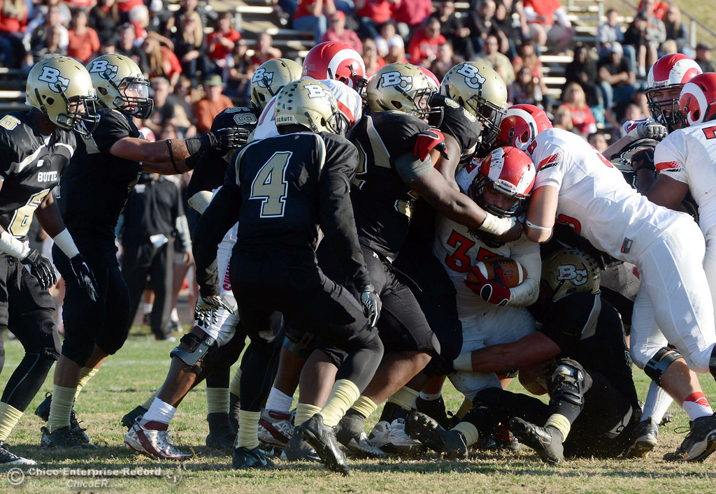 . Butte College tackle against Fresno City College\'s #33 Dakota Gordon (center) in the fourth quarter of their football game at Butte\'s Cowan Stadium Saturday, November 30, 2013 in Butte Valley, Calif.  (Jason Halley/Chico Enterprise-Record)