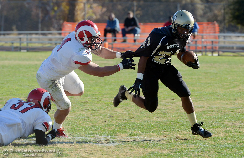 . Butte College\'s #21 Marvel Harris (right) is tackled against Fresno City College\'s #4 Isaac Sarate (center) and #37 Gerald Nutt (left) in the third quarter of their football game at Butte\'s Cowan Stadium Saturday, November 30, 2013 in Butte Valley, Calif.  (Jason Halley/Chico Enterprise-Record)