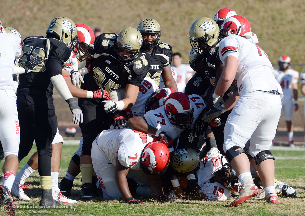 . Butte College\'s #95 Mark Rosenquist (center) piles on the crowd against Fresno City College in the first quarter of their football game at Butte\'s Cowan Stadium Saturday, November 30, 2013 in Butte Valley, Calif.  (Jason Halley/Chico Enterprise-Record)
