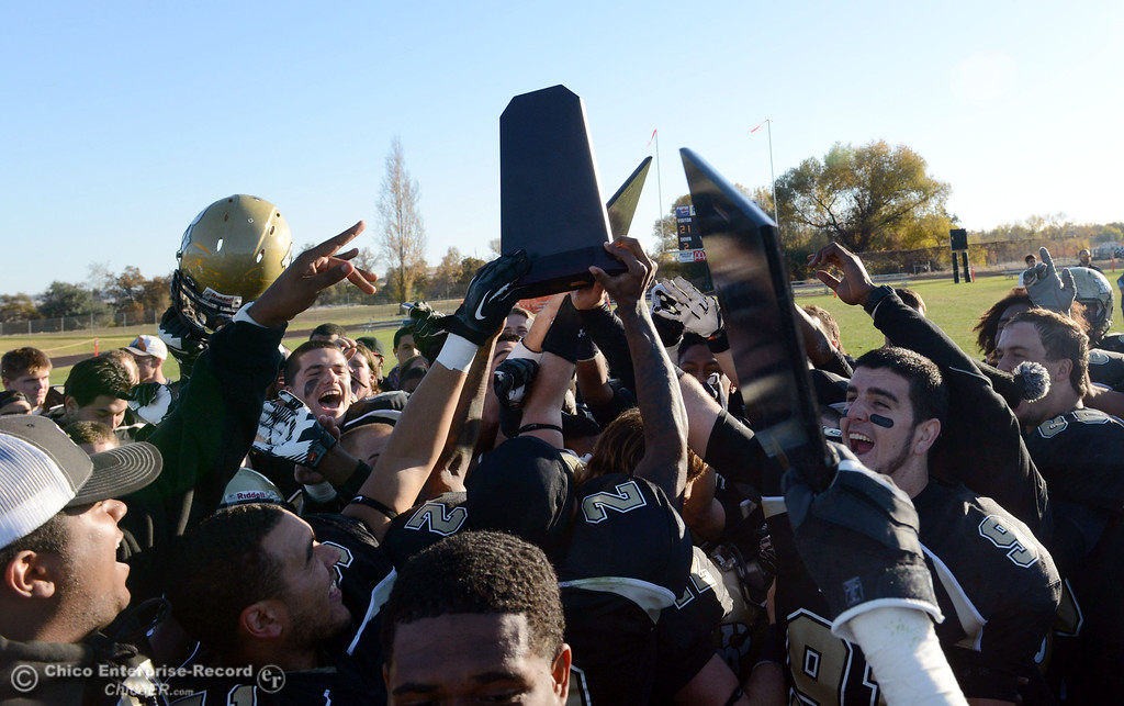 . Butte College accepts the trophy in their win against Fresno City College at the end of their football game at Butte\'s Cowan Stadium Saturday, November 30, 2013 in Butte Valley, Calif.  (Jason Halley/Chico Enterprise-Record)