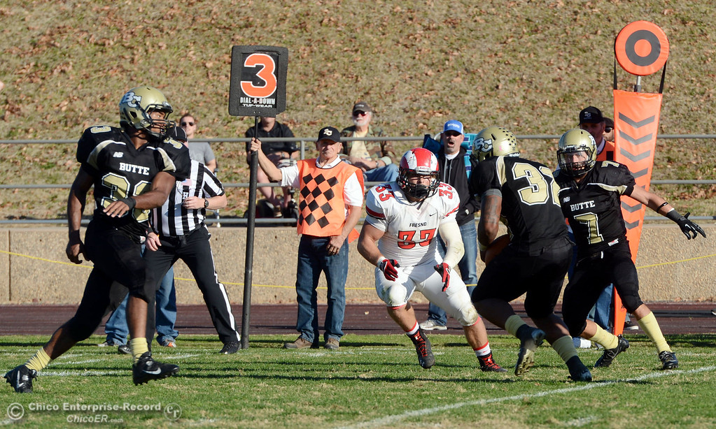 . Butte College\'s #32 Brian Anderson (center) picks up a interception against Fresno City College in the third quarter of their football game at Butte\'s Cowan Stadium Saturday, November 30, 2013 in Butte Valley, Calif.  (Jason Halley/Chico Enterprise-Record)