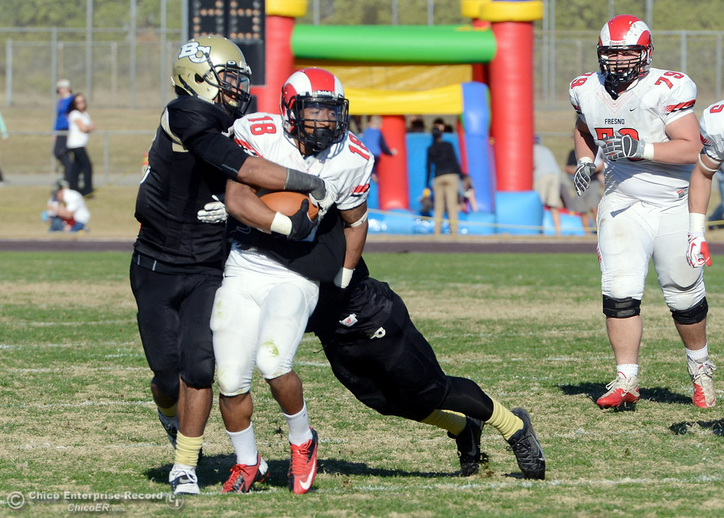 . Butte College\'s #3 London Muse (left) and #4 Chris Edwards (right) tackle against Fresno City College\'s #18 Micah Ledezma (center) in the third quarter of their football game at Butte\'s Cowan Stadium Saturday, November 30, 2013 in Butte Valley, Calif.  (Jason Halley/Chico Enterprise-Record)