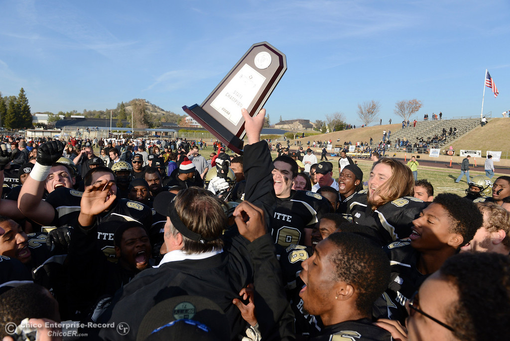 . Butte College head coach Jeff Jordan (center) holds up the championship trophy in their win against Fullerton College at the end of the fourth quarter of their CCCAA football state championship final at Butte\'s Cowan Stadium Saturday, December 14, 2013 in Butte Valley, Calif. (Jason Halley/Chico Enterprise-Record)