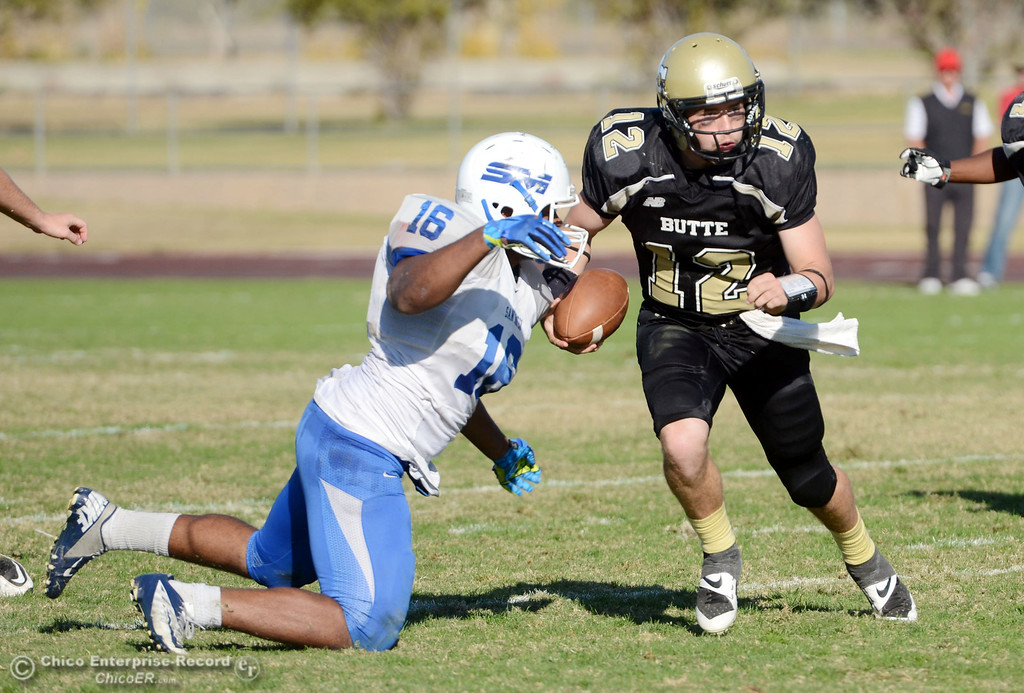 . Butte College\'s #12 Thomas Stuart (right) is tackled against College of San Mateo\'s #16 Michael Spivey (left) in the third quarter of their football game at Butte\'s Cowan Stadium Saturday, November 2, 2013 in Oroville, Calif.  (Jason Halley/Chico Enterprise-Record)