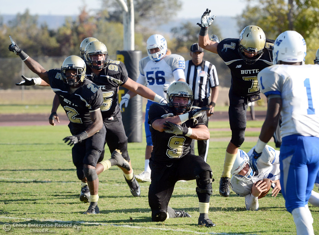 . Butte College\'s #2 Deonte Flemings, #95 Mark Rosenquist, #9 Tyler Adair, and #7 Ryan Holland (left to right) celebrate Adair\'s sack against San Mateo College\'s #7  Casey Wichman (right bottom) to end the final play in the fourth quarter of their football game at Butte\'s Cowan Stadium Saturday, November 2, 2013 in Oroville, Calif.  (Jason Halley/Chico Enterprise-Record)