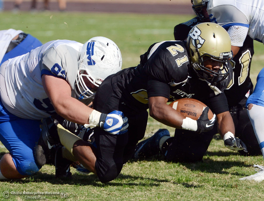 . Butte College\'s #21 Marvel Harris (right) is tackled against College of San Mateo\'s #92 Trevor Kelly (left) in the second quarter of their football game at Butte\'s Cowan Stadium Saturday, November 2, 2013 in Oroville, Calif.  (Jason Halley/Chico Enterprise-Record)