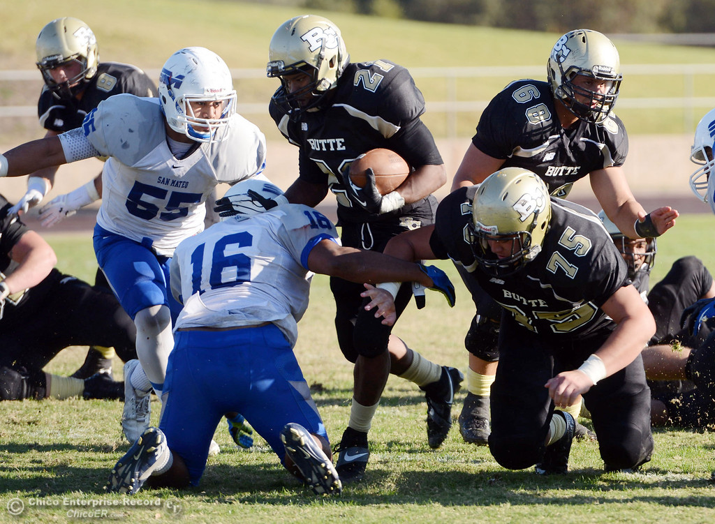 . Butte College\'s #21 Marvel Harris (left) is tackled against College of San Mateo\'s #16 Michael Spivey (bottom) and #55 Mosa LIkio (left) along with Butte\'s #75 Jacob Vazquez (right) and #68 Eli Thom (right top) in the fourth quarter of their football game at Butte\'s Cowan Stadium Saturday, November 2, 2013 in Oroville, Calif.  (Jason Halley/Chico Enterprise-Record)