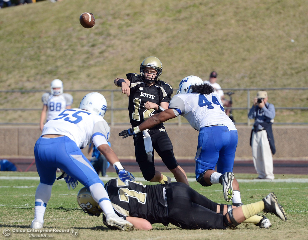 . Butte College\'s #12 Thomas Stuart (center) throws a pass against College of San Mateo in the second quarter of their football game at Butte\'s Cowan Stadium Saturday, November 2, 2013 in Oroville, Calif.  (Jason Halley/Chico Enterprise-Record)