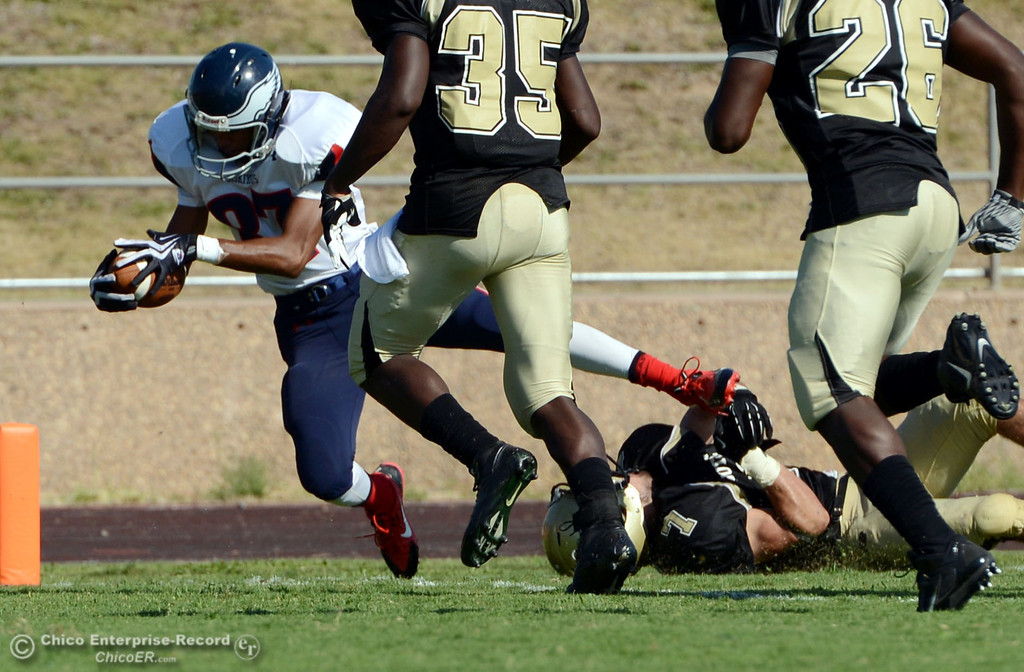 . Butte College\'s #7 Ryan Holland (right) is unable to stop against College of the Siskiyous\' #87 Kendrick Murphy (left) from scoring a touchdown in the fourth quarter of their football game at Butte\'s Cowan Stadium on Saturday, September 14, 2013, in Oroville, Calif. (Jason Halley/Chico Enterprise-Record)