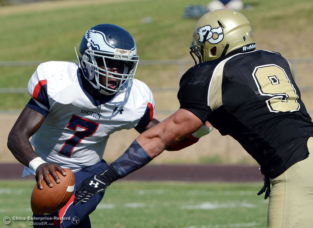 . Butte College\'s #9 Tyler Adair (right) puts pressure against College of the Siskiyous\' #7 Warren Johnson (left) in the third quarter of their football game at Butte\'s Cowan Stadium on Saturday, September 14, 2013, in Oroville, Calif. (Jason Halley/Chico Enterprise-Record)