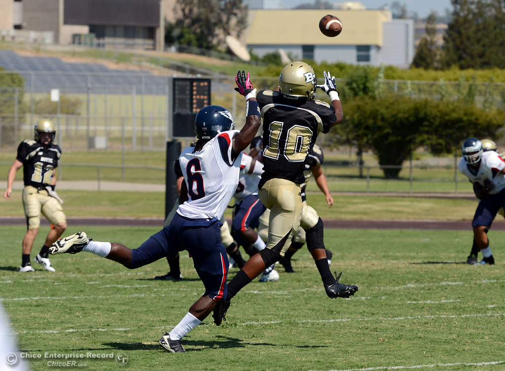 . Butte College\'s #10 CJ Grice (right) completes a catch against College of the Siskiyous\' #6 Michael Everett (left) in the first quarter of their football game at Butte\'s Cowan Stadium on Saturday, September 14, 2013, in Oroville, Calif. (Jason Halley/Chico Enterprise-Record)