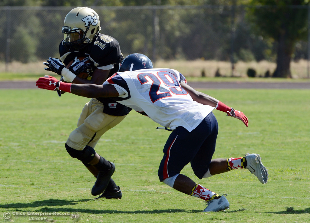 . Butte College\'s #10 CJ Grice (left) is tackled against College of the Siskiyous\' #29 Yves Nguessan (right) in the second quarter of their football game at Butte\'s Cowan Stadium on Saturday, September 14, 2013, in Oroville, Calif. (Jason Halley/Chico Enterprise-Record)