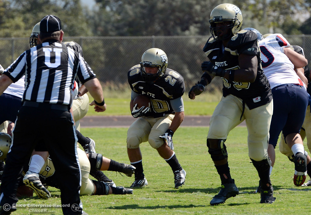 . Butte College\'s #20 Armand Bokitch (center) rushes against College of the Siskiyous in the second quarter of their football game at Butte\'s Cowan Stadium on Saturday, September 14, 2013, in Oroville, Calif. (Jason Halley/Chico Enterprise-Record)