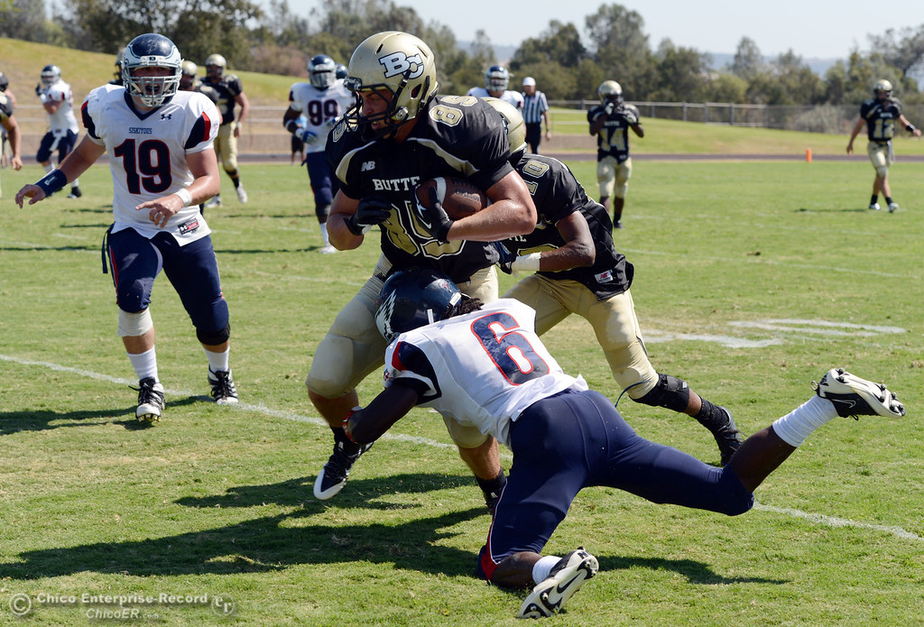 . Butte College\'s #85 Richard Murphy (center) is tackled against College of the Siskiyous\' #6 Michael Everett (bottom) in the second quarter of their football game at Butte\'s Cowan Stadium on Saturday, September 14, 2013, in Oroville, Calif. (Jason Halley/Chico Enterprise-Record)