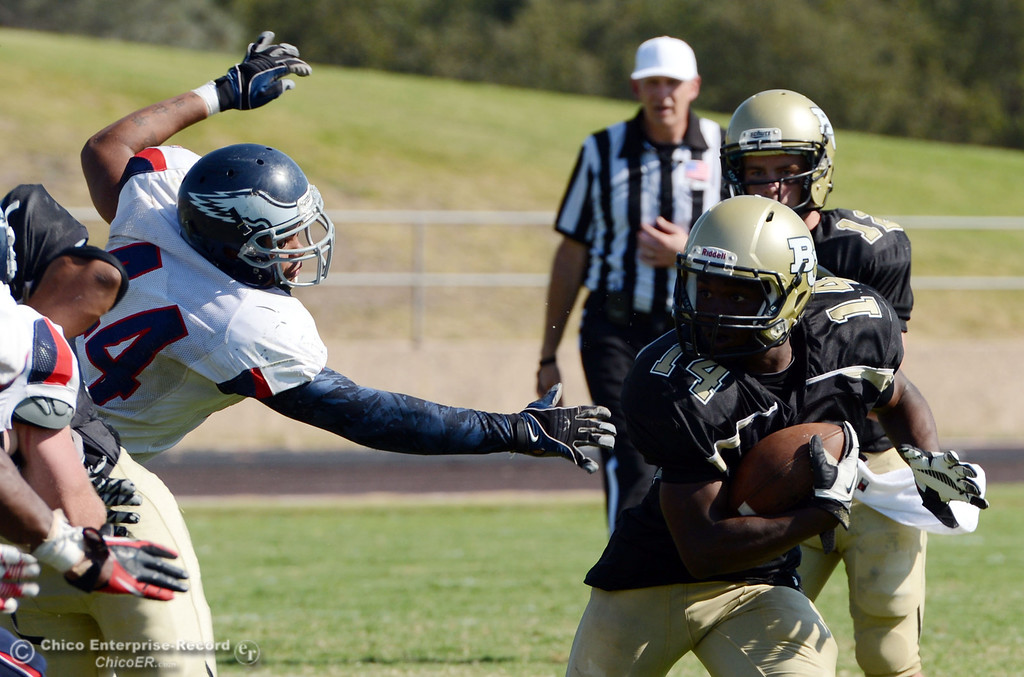 . Butte College\'s #14Robert Frazier (right) breaks a tackle against College of the Siskiyous\' #44 Justin Merriweather (left) in the third quarter of their football game at Butte\'s Cowan Stadium on Saturday, September 14, 2013, in Oroville, Calif. (Jason Halley/Chico Enterprise-Record)