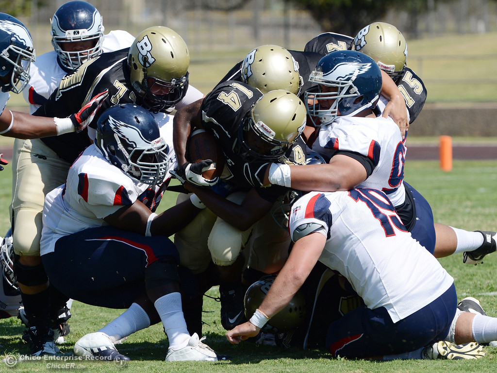 . Butte College\'s #14 Robert Frazier (center) is tackled against College of the Siskiyous in the first quarter of their football game at Butte\'s Cowan Stadium on Saturday, September 14, 2013, in Oroville, Calif. (Jason Halley/Chico Enterprise-Record)