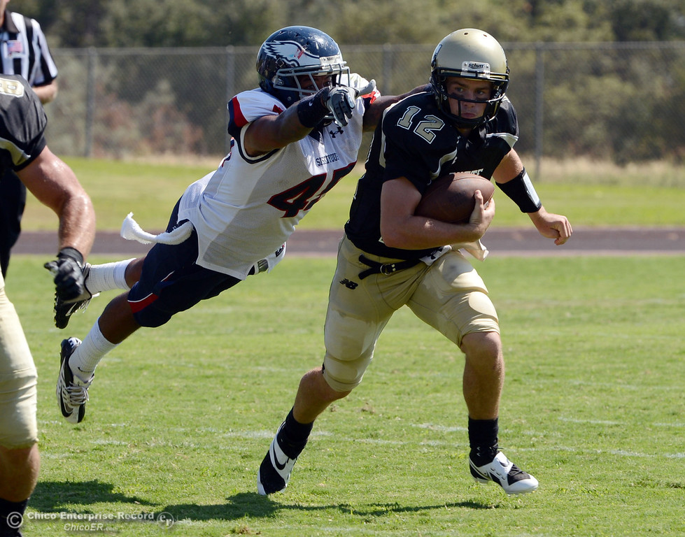 . Butte College\'s #12 Thomas Stuart (right) breaks a tackle against College of the Siskiyous\' #45 Kerry Stabler (left) in the second quarter of their football game at Butte\'s Cowan Stadium on Saturday, September 14, 2013, in Oroville, Calif. (Jason Halley/Chico Enterprise-Record)