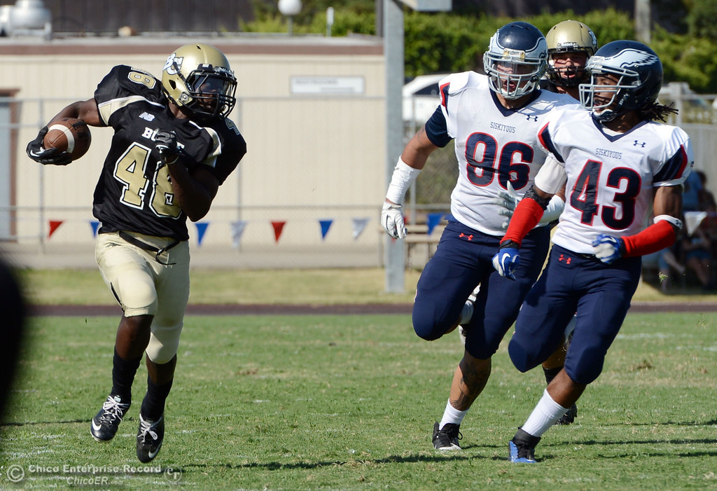 . Butte College\'s #48 Michael Faggett (left) rushes against College of the Siskiyous\' #86 Dexter Barcus-Glover (center) and #43 Marcus McCoy (right) in the fourth quarter of their football game at Butte\'s Cowan Stadium on Saturday, September 14, 2013, in Oroville, Calif. (Jason Halley/Chico Enterprise-Record)