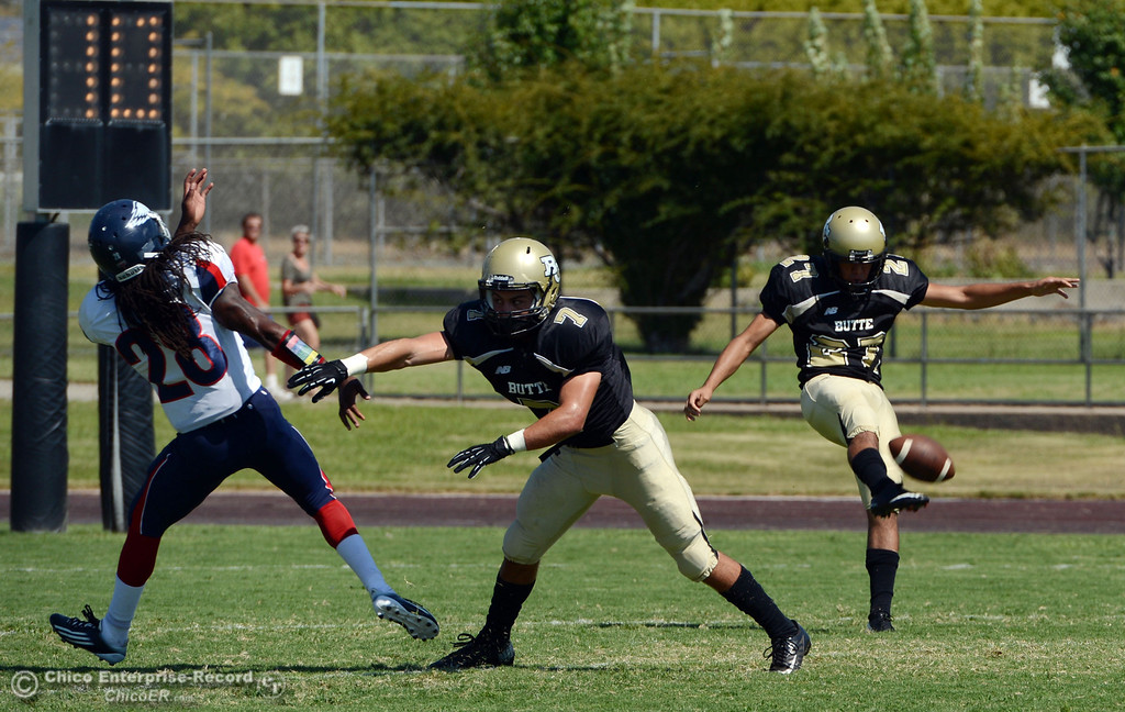 . Butte College\'s #27 Rigoberto Sanchez punts as #7 Ryan Holland (center) blocks against College of the Siskiyous\' #28 Edwin McKinney (left) in the first quarter of their football game at Butte\'s Cowan Stadium on Saturday, September 14, 2013, in Oroville, Calif. (Jason Halley/Chico Enterprise-Record)