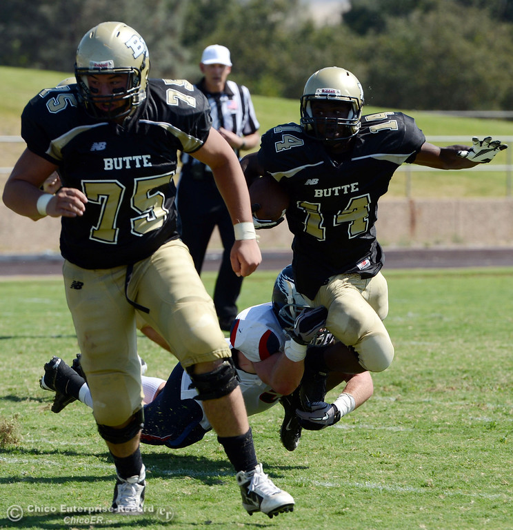 . Butte College\'s #75 Jacob Vazquez (left) leads ahead of #14 Robert Frazier (right) who is tackled against College of the Siskiyous\' #52 Jason Syverson (bottom) in the second quarter of their football game at Butte\'s Cowan Stadium on Saturday, September 14, 2013, in Oroville, Calif. (Jason Halley/Chico Enterprise-Record)