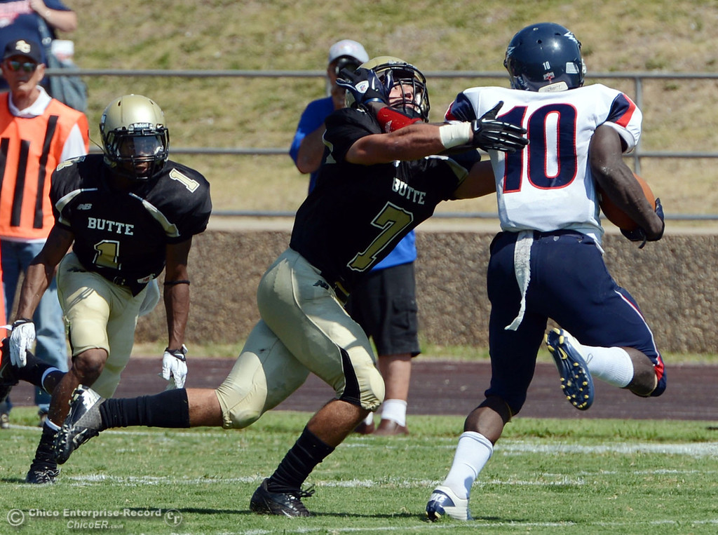 . Butte College\'s #1 Wes McCoy (left) watches #7 Ryan Holland (center) tackle against College of the Siskiyous\' #10 Kirt Terry-Springs (right) in the first quarter of their football game at Butte\'s Cowan Stadium on Saturday, September 14, 2013, in Oroville, Calif. (Jason Halley/Chico Enterprise-Record)