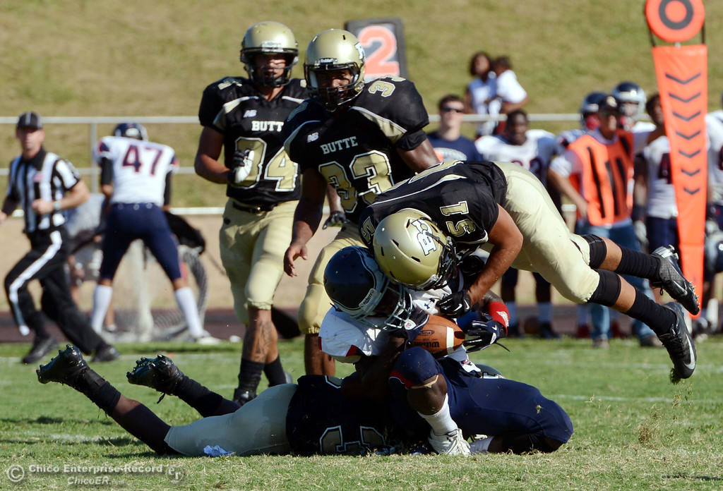 . Butte College\'s #35 Zach WIlliams (left) and #51 Izaya Johnson (right) tackle against College of the Siskiyous\' #10 Kirt Terry-Springs (center) who was still able to complete the catch in the fourth quarter of their football game at Butte\'s Cowan Stadium on Saturday, September 14, 2013, in Oroville, Calif. (Jason Halley/Chico Enterprise-Record)
