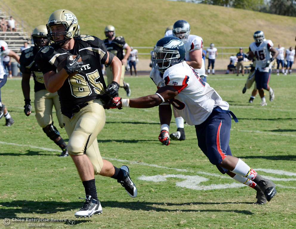 . Butte College\'s #85 Richard Murphy (left) rushes against College of the Siskiyous\' #58 Tyrese Lyons (right) in the third quarter of their football game at Butte\'s Cowan Stadium on Saturday, September 14, 2013, in Oroville, Calif. (Jason Halley/Chico Enterprise-Record)