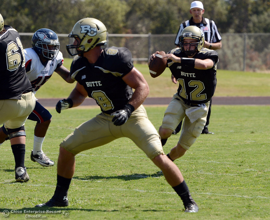 . Butte College\'s #12 Thomas Stuart (right) scrambles against College of the Siskiyous in the second quarter of their football game at Butte\'s Cowan Stadium on Saturday, September 14, 2013, in Oroville, Calif. (Jason Halley/Chico Enterprise-Record)