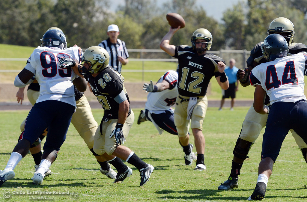 . Butte College\'s #12 Thomas Stuart (center) throws a pass against College of the Siskiyous in the second quarter of their football game at Butte\'s Cowan Stadium on Saturday, September 14, 2013, in Oroville, Calif. (Jason Halley/Chico Enterprise-Record)