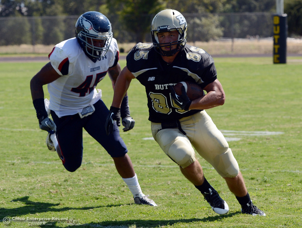 . Butte College\'s #85 Ricahrd Murphy (right) rushes against College of the Siskiyous\' #45 Kerry Stabler (left) in the second quarter of their football game at Butte\'s Cowan Stadium on Saturday, September 14, 2013, in Oroville, Calif. (Jason Halley/Chico Enterprise-Record)