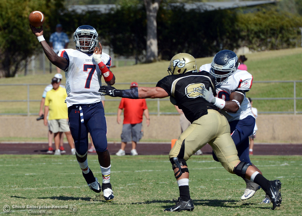 . College of the Siskiyous\' #7 Warren Johnson (left) throws a pass against Butte College in the third quarter of their football game at Butte\'s Cowan Stadium on Saturday, September 14, 2013, in Oroville, Calif. (Jason Halley/Chico Enterprise-Record)